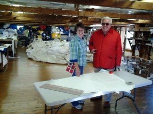 Bill Miller with Michele Stevens in the sail loft. Behind them employees are at work making a sail for the newly built replica of Columbia – an American schooner which competed against Bluenose in the International Fisherman's Races in 1920's